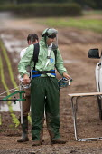 A farmworker wearing protective clothing (Waterproof Spray Suit) training in the use of a backpack Pesticide applicator, Warwickshire - John Harris - 2010s,2014,agricultural,agriculture,agrochemicals,apparel,arable,backpack,capitalism,capitalist,chemical,chemicals,clothing,crop,crops,EBF,Economic,Economy,employee,employees,Employment,eni,environmen
