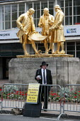 Preaching the Gospel beneith the The gilded bronze statue of the industralists Matthew Boulton, James Watt and William Murdoch by William Bloye and Raymond Forbes-Kings, nicknamed 'The Golden Boys' Co... - John Harris - 29-09-2014
