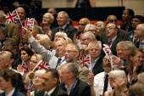 Delegates waving union Jack flags, David Cameron MP speaking, Conservative Party Conference, ICC Birmingham - John Harris - 01-10-2014