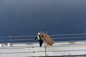 Construction worker with insulation on the roof of a new development, Wellesbourne Distribution Park, Warwickshire - John Harris - 18-12-2014