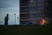 A youth walking past tower blocks, Druids Heath, Birmingham - John Harris - ,2010s,2015,adolescence,adolescent,adolescents,alone,at,Birmingham,boy,boys,child,CHILDHOOD,children,cities,city,council estate,council services,council estate,council services,dark,Druid,Druids,dusk,