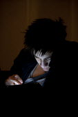 Teenager using an Ipad online at night. - John Harris - 13-02-2015
