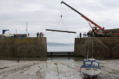 Crane lifting The Baulks which block the entrance to the harbour and provide protection against winter storms, Mousehole harbour, Cornwall - John Harris - 22-03-2015