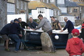Fishermen lifting and carrying small boats. Launching the fishing fleet at the start of the season, Mousehole harbour, Cornwall - John Harris - 21-03-2015