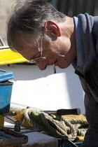 Fishermen repairing an engine of a fishing boat, Mousehole harbour, Cornwall - John Harris - 2010s,2015,adult,adults,age,ageing population,boat,boats,CIGARETTE,cigarettes,coast,coastal,coasts,crew,crewman,crewmen,crewmenmaritime,dock,docks,dockside,EARNINGS,EBF,Economic,Economy,elderly,employ