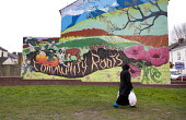 A woman walking home past a mural of Community Roots, trees and animals painted onto the end of a terrace. Handsworth, Birmingham - John Harris - 2010s,2015,ACE,art,arts,BAME,BAMEs,Birmingham,Black,BME,bmes,cities,city,communities,Community,cultural,culture,diversity,ethnic,ethnicity,FEMALE,home,house,houses,housing,Housing Estate,ISLAM,ISLAMIC