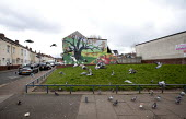 Feral pigeons taking off, a mural of trees and fruit painted onto the end of a terrace. Handsworth, Birmingham - John Harris - 01-04-2015
