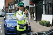 Civil Enforcement Officer photographing a parked car with a handheld digital compliance device, Stratford Upon Avon. - John Harris - 2010s,2015,AUTO,AUTOMOBILE,AUTOMOBILES,AUTOMOTIVE,car,cars,check,checking,civil enforcement officer,CLJ,compliance,COMPUTE,computer,computers,computing,council,Council Services,Council Services,device