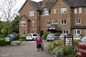 A resident walking into town from retirement flats in sheltered housing, Stratford Upon Avon, Warwickshire - John Harris - 02-06-2015