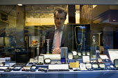 An assistant selecting jewellery for a customer from the window display of a prestige jewellers, Stratford Upon Avon, Warwickshire - John Harris - 2010s,2015,AFFLUENCE,AFFLUENT,antique,antiques,assistant,assistant assistants,ASSISTANTS,bought,Bourgeoisie,buy,buyer,buyers,buying,Carat of Gold,choice,choosing,collectable,collecting,collection,comm