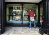 Window cleaner cleaning the shop window Stratford-Upon-Avon, Warwickshire - John Harris - 2010s,2015,cleaner,cleaners,cleaning,cleansing,EARNINGS,EBF,Economic,Economy,employee,employees,Employment,EQUALITY,Income,INCOMES,inequality,jeweler,jewelers,Jeweller,Jewellers,jewellery,jewelry,jewe