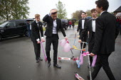 Pupils arriving at their High school Prom on scooters in the rain, at the end of the last year at school, Henley in Arden, Warwickshire - John Harris - 2010s,2015,ACE,adolescence,adolescent,adolescents,ARRIVAL,arrivals,arrive,arrived,arrives,arriving,boy,boys,child,CHILDHOOD,children,culture,dressed up,edu,educate,educating,education,educational,End