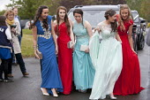 Pupils arriving at their High school Prom in the rain at the end of the last year at school, Henley in Arden, Warwickshire - John Harris - 2010s,2015,ACE,adolescence,adolescent,adolescents,ARRIVAL,arrivals,arrive,arrived,arrives,arriving,child,CHILDHOOD,children,culture,Dress,dressed up,dresses,edu,educate,educating,education,educational