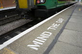 Mind the gap warning on the railway station platform as a train departs, London and Midland line, Stratford-upon-Avon, Warwickshire - John Harris - 10-06-2015