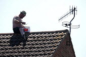A man balancing on the apex of his roof sealing tiles with Grip It tile adhesive. Stratford-Upon-Avon, Warwickshire - John Harris - 11-06-2015