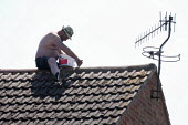 A man balancing on the apex of his roof sealing tiles with Grip It tile adhesive. Stratford-Upon-Avon, Warwickshire - John Harris - 2010s,2015,apex,DIY,do it yourself,fill,filling,fills,grouting,home,house,houses,leak,leaks,Leisure,LFL,LIFE,maintaining,maintenance,male,man,men,PEOPLE,person,persons,RECREATION,RECREATIONAL,renewal,