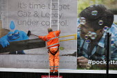 Worker pasting a new advertisement onto a billboard, Birmingham - John Harris - 26-07-2015