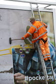 Worker pasting a new advertisement onto a billboard, Birmingham - John Harris - 2010s,2015,advertisement,advertisements,advertising,billboard,billboards,Birmingham,cities,city,EARNINGS,EBF,Economic,Economy,employee,employees,Employment,EQUALITY,fitter,fitters,fitting,hazard,hazar