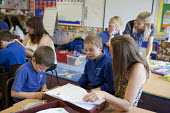Parent going through exercise books. Open Day for parents of pupils at primary school, St Richards First School, Evesham, Worcestershire - John Harris - 06-07-2015