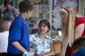 Head teacher talking to parent going through exercise books. Open Day for parents of pupils at primary school, St Richards First School, Evesham, Worcestershire - John Harris - 06-07-2015