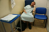 Patient waiting for an operation, pre op asssement, Warwick Hospital - John Harris - 2010s,2015,bored,boredom,boring,care,disinterested,gown,gowns,HEA,Health,HEALTH SERVICES,healthcare,hospital,hospitals,male,man,men,national health service,NHS,notes,operation,operations,patient,patie