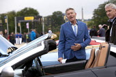 Tiff Needell TV presenter looking at Salon Prive Supercar Show Blenheim Palace Oxfordshire - John Harris - wealth,2010s,2015,AFFLUENCE,AFFLUENT,AUTO,AUTOMOBILE,AUTOMOBILES,AUTOMOTIVE,Bourgeoisie,broadcaster,car,cars,communicating,communication,conversation,conversations,dialogue,discourse,DISCUSS,discusses
