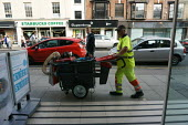 A street cleaner pushing his cart, Stratford upon Avon - John Harris - 2010s,2015,cleaner,cleaners,CLEANING,cleansing,EARNINGS,employee,employees,Employment,EQUALITY,Income,INCOMES,inequality,job,jobs,LBR,living wage,Low Pay,Low Income,low paid,Low Pay,male,man,men,older