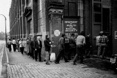 Unemployed queuing for social security, Coventry 1981, as engineering factories close and jobs are lost - John Harris - 1980s,1981,Benefit,BENEFITS,cities,city,Coventry,deindustrialisation,Deindustrialization,dole,DOWNTURN,EBF,Economic,economic crisis,Economy,employee,employees,Employment,engineering,factories,FACTORY,