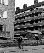 Disabled pensioner on crumbling housing estate Toxteth, Liverpool 1981, an area of high unemployment multiple deprivation poor health and high dependency on welfare - John Harris - ,1980s,1981,adult,adults,age,ageing population,Deprivation,disabilities,disability,disable,disabled,disablement,elderly,EQUALITY,excluded,exclusion,fail,frailty,HARDSHIP,housing,impoverished,impoveris