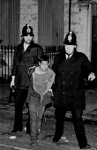 Police arrest a black youth during a weekend of some of the worst inner city urban riots in mainland Britain. Many accuse the police of racism. Toxteth riots, Liverpool 1981 - John Harris - ,1980s,1981,adult,adults,arrest,arrested,arresting,BAME,BAMEs,bigotry,Black,BME,bmes,boy,boys,child,CHILDHOOD,children,civil,CLJ,CLJ crime law and justice,conflict,conflicts,DISCRIMINATION,diversity,e