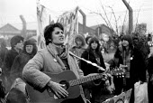 Embrace the base women protest at Greenham Common USAF American Airforce Base from which cruse missile launchers were deployed. 1982 Protestor singing and playing guitar. - John Harris - 1980s,1982,ACE,activist,activists,Air force,Airbase,airbases,Airforce,American,americans,Anti War,Antiwar,armed forces,atomic,bomb,BOMBS,Campaign,Campaign for Nuclear Disarmament,campaigner,campaigner