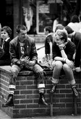 Unemployed youth with doc martin boots and union jack badges Coventry 1982, shopping precinct as recession in manufacturing intensifies - John Harris - ,1980s,1982,adolescence,adolescent,adolescents,BADGE,badges,bigotry,bought,buy,buyer,buyers,buying,capitalism,capitalist,commodities,commodity,consumer,consumers,Coventry,customer,customers,deindustri