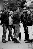 Unemployed youth with doc martin boots and union jack badges Coventry shopping precinct as recession in manufacturing intensifies 1982 - John Harris - ,1980s,1982,adolescence,adolescent,adolescents,BADGE,badges,bigotry,bought,buy,buyer,buyers,buying,capitalism,commodities,commodity,consumer,consumers,customer,customers,deindustrialisation,Deindustri