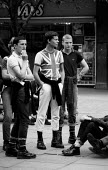 Skin heads with doc martin boots and union jack badges hanging around Coventry shopping precinct 1982as recession in manufacturing intensifies and unemployed youth are targeted by right wing political... - John Harris - 30-03-1982