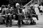 Asian men sitting in Coventry shopping precinct 1982 whilst skinheads with doc martin boots and union jack badges gather nearby. The recession intensifies and unemployed youth are targeted by right wi... - John Harris - 30-03-1982