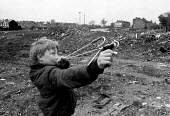 Youth firing catapult on waste ground whilst playing truant from school. Local authority Housing clearance area Birmingham - John Harris - 01-04-1983