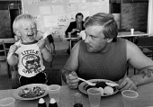 Striking miners eating in a soup kitchen funded by donations from supporters of the strike. Miners Welfare, Keresley Colliery, Coventry 1984 - John Harris - 1980s,1984,boy,boys,canteen,CANTEENS,child,CHILDHOOD,children,collieries,Colliery,DAD,DADDIES,DADDY,DADS,disputes,donations,eat,eating,families,FAMILY,father,FATHERHOOD,fathers,food,FOODS,funny,having