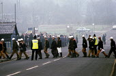 Picket of striking miners at Silverwood Colliery as working miners cross the road at the end of their shift. Miners strike South Yorkshire coalfield - John Harris - 1980s,1985,adult,adults,breaker,breakers,clj law,coal industry,coalindustry,collieries,Colliery,cross,crosses,crossing,DISPUTE,DISPUTES,highway,INDUSTRIAL DISPUTE,Mass picketing,Mass pickets,MATURE,me