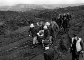 Emergency services rescue a miner buried alive whilst riddling for coal amongst the pit waste for fuel during the year long Miners strike. Silverwood colliery, Yorkshire - John Harris - 1980s,1985,accident accidents,adult,adults,CLJ,coal,coal industry,coalindustry,collieries,colliery,DIA,disputes,Emergency,fire brigade,firefighter,firefighter firefighters,firefighters,fireman,firemen