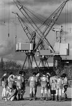 Shipyard football team training, 1986, Kvaerner Govan dockside cranes, Clydeside Glasgow - John Harris - 18-05-1986