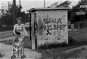 Mother and child walking passed graffiti on a bus stop in Seascale, the nearest town to the radioactive waste reprocessing plant at Sellafield (formally Windscale) British Nuclear Fuels Cumbria. Clust... - John Harris - 26-07-1986