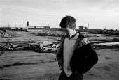 Youth wandering across derelict part demolished site of the KME factory on the edge of the Kirkby housing estate, an area of high unemployment, poverty, multiple deprivation and dependency on welfare.... - John Harris - ,1980s,1986,capitalism,capitalist,deindustrialisation,Deindustrialization,DEMOLISH,demolished,demolition,Deprivation,derelict,dereliction,DEVELOPMENT,DOWNTURN,EBF,Economic,Economy,eni environmental is
