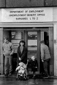 Mother and children and claiments unemployment benefit office Kirby Liverpool 1986 An area of high unemployment, poverty, multiple deprivation and dependency on welfare - John Harris - 04-11-1986