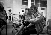 Unemployed parents with child waiting at a DHSS benefit office Coventry as the recession intensifies 1982 - John Harris - 24-12-1986