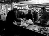 Pensioners and homeless mooching, trying to find edible food discarded by market traders at the end of the day to supplement their low income. The Bull Ring Shopping Centre Birmingham 1987 - John Harris - 26-03-1987
