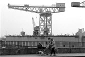 Women with push chair and bicycle walking past the VSEL shipyard which builds the Trident nuclear submarine in the background. Barrow in Furness - John Harris - ,1980s,1988,adult,adults,and,atomic,babies,baby,capitalism,capitalist,CARE,carer,carers,child,Child Care,childcare,CHILDHOOD,CHILDMINDING,children,Crane,Cranes,defence,defense,DOCK,docks,dockside,EARL