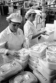 Filling tubs of with ice cream on the production line. Ice cream factory Fiesta Foods Ltd West Midlands - John Harris - ,1980s,1988,capitalism,capitalist,EARNINGS,EBF economy business,EQUALITY,FACTORIES,factory,female,Filling,food,FOODS,Income,INCOMES,Industries,industry,inequality,job,jobs,LAB LBR work,living wage,Low