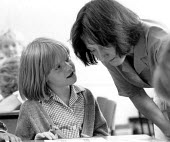 Teacher listening to a question from a pupil during a lesson at a Primary School - John Harris - 16-06-1989