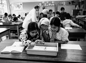 Asian girls working together on a science project School Mosley Birmingham - John Harris - 1980s,1988,Asian,BAME,BAMEs,Birmingham,black,BME,bmes,child,CHILDHOOD,children,cities,city,class,classroom,CLASSROOMS,diversity,EDU education,ethnic,ethnicity,Experiment,Experimenting,female,females,g