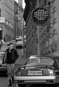 Youth passing an expensive car parked on the pavement outside a wine bar, Little Germany, an area where many German Jews settled, now redeveloped for financial services and business. Bradford - John Harris - ,1980s,1988,AFFLUENCE,AFFLUENT,AUTO,AUTOMOBILE,AUTOMOBILES,AUTOMOTIVE,Bourgeoisie,car,CARS,cities,city,class,EBF economy business & finance,elite,elitism,EQUALITY,GERMAN,Germany,high,high income,incom